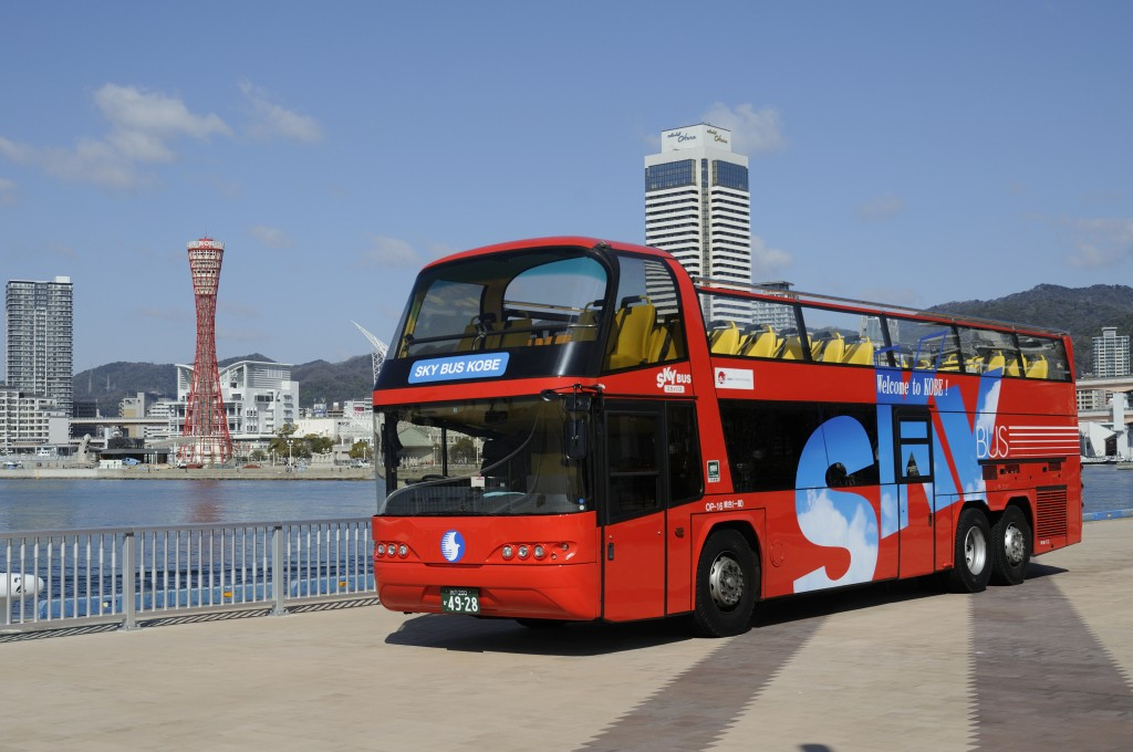 A two-story open-top bus with a beautiful red-color body.